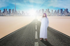 Muslim man talking on smartphone at road. Business muslim man with islamic clothes talking on smartphone while standing on the road Stock Photography