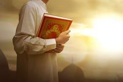 Muslim man in traditional dress holding holy book Koran Stock Photos