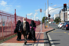 Muslim man walks with two muslim woman with fully body cover (Bu Royalty Free Stock Photo