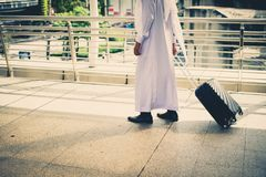 Muslim man wear white coat walking on public street with black luggage. business travel. Concept Royalty Free Stock Photos