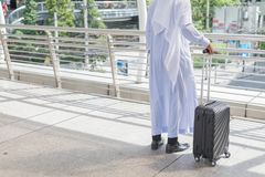 Muslim man wear white coat walking on public street with black luggage. Business travel concept Stock Images