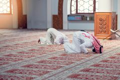Muslim man and woman praying for Allah in the mosque together. Muslim men and women praying for Allah in the mosque together stock photo