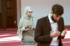 Muslim man and woman praying in mosque Stock Images