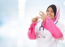 Muslim manipulerar fyllning injektionssprutan Royaltyfria Bilder