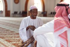 Muslim men praying with holy books in mosque stock images