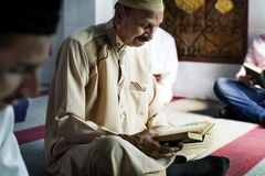 Muslim men reading Quran during Ramadan royalty free stock images