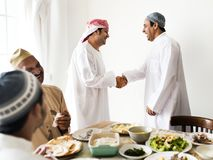 Muslim men shaking hands at lunchtime stock image