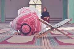 Muslim man and woman praying for Allah in the mosque together. Muslim men and women praying for Allah in the mosque together Royalty Free Stock Photography