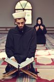 Muslim man and woman praying for Allah in the mosque together Stock Photography