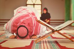 Muslim man and woman praying for Allah in the mosque together. Muslim men and women praying for Allah in the mosque together Royalty Free Stock Image