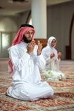 Muslim man and woman praying in mosque Royalty Free Stock Photo