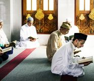 Muslim men and women reading Quran during Ramadan royalty free stock photography