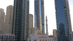 Muslim mosque and glass skyscrapers in Dubai Marina in United Arab Emirates, Urban landscape glass facades skyscrapers. Muslim mosque and modern glass stock video footage