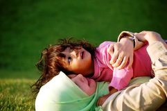 A Muslim Mother and Daughter. A mother and her daughter lying on the grass at the playground Stock Images