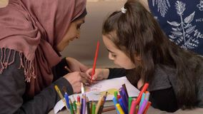 Muslim mother and daughter lie on the couch and paint with colored pencils, happy family concept, home comfort in the. Background, side view 50 fps 4k stock video footage