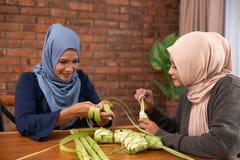 Muslim making traditional ketupat or rice cake royalty free stock images