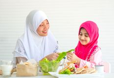 Muslim mother discuss and teach about vegetable for food to her little girl with white background stock photo