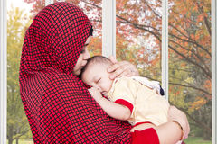 Muslim mother lull her baby at home. Portrait of muslim mother wearing veil and lull her baby near the window at home royalty free stock photos