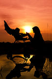 Muslim mother playing with her baby. During sunset at park silhouetted Stock Photos
