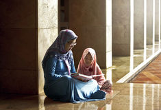 Muslim mother teach her daughter reading koran Royalty Free Stock Photo