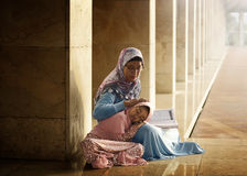 Muslim mother teach her daughter reading koran. Inside the mosque royalty free stock photos