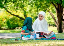 Muslim mother teach her daughter to read religion textbook for understanding the way of good life. They stay in the green garden stock photo