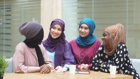 Muslim multiethnic female representatives posing in lobby of business centre. Diverse muslim multiethnic female representatives participating in international stock footage