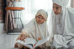 Muslim parent and daughter reading quran stock photography