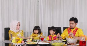Muslim parents feed their kids during dinner. Two young happy muslim parents feeding their children during dinner together in dining room while wearing islamic stock footage