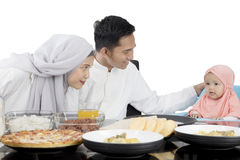 Muslim parents having meal with daughter Stock Photos