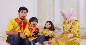 Muslim parents and kids play video games. Two young muslim parents and their children playing video games together while sitting on the sofa at home. Shot in 4k stock video footage