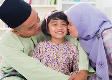 Muslim parents kissing child. Stock Photography