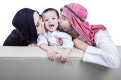 Muslim parents kissing their son cheek. Portrait of two middle eastern parents sitting on the sofa while kissing their son cheek, isolated on white background Stock Image