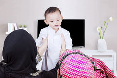 Muslim parents lifting son in living room Stock Photo