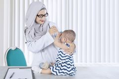 Muslim pediatrician checking her patient in the clinic. Muslim pediatrician using a digital thermometer for checking temperature of her patient in the clinic Stock Photography