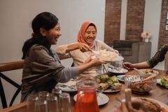 Muslim people passing food during fasting dinner