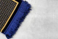 Muslim prayer rug. On gray background Royalty Free Stock Photos