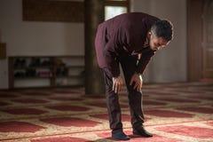 Muslim praying. Humble Muslim man praying peacefully in a gorgeous Mosque Stock Photo