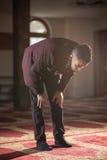 Muslim praying. Humble Muslim man praying peacefully in a gorgeous Mosque Stock Image