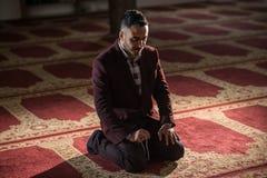 Muslim praying. Humble Muslim man praying peacefully in a gorgeous Mosque Royalty Free Stock Image