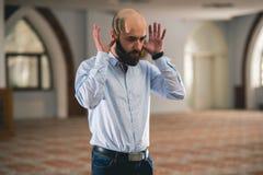Muslim praying. Young Muslim man praying in mosque Royalty Free Stock Photo