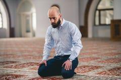 Muslim praying. Young Muslim man praying in mosque Stock Image