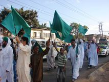 Muslim raising green flags Royalty Free Stock Image