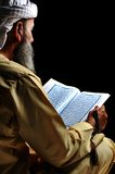 Muslim reading Koran. On dark royalty free stock photo