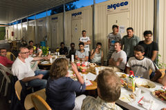 Muslim refugees and German volunteers sit together eating dinner during Ramadan fasting month. Scharnhausen, Germany - June 22.06.2016: Male Muslim refugees and