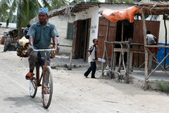 Muslim riding bike over dirt road fishing village Stock Photo