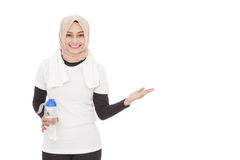 Muslim sporty woman holding a bottle of mineral water while pres Royalty Free Stock Photography