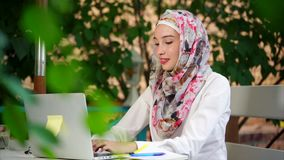 Muslim student in hijab writes an essay on a laptop in the park on a summer day stock video