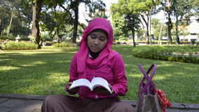 Muslim student reading book outdoors Royalty Free Stock Photography