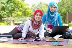 Muslim students studying. Two young muslim students in traditional Hijabs studying with book and laptop in park Royalty Free Stock Photo